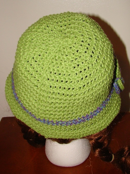 back view of green hat with purple stripe and purple and green flower