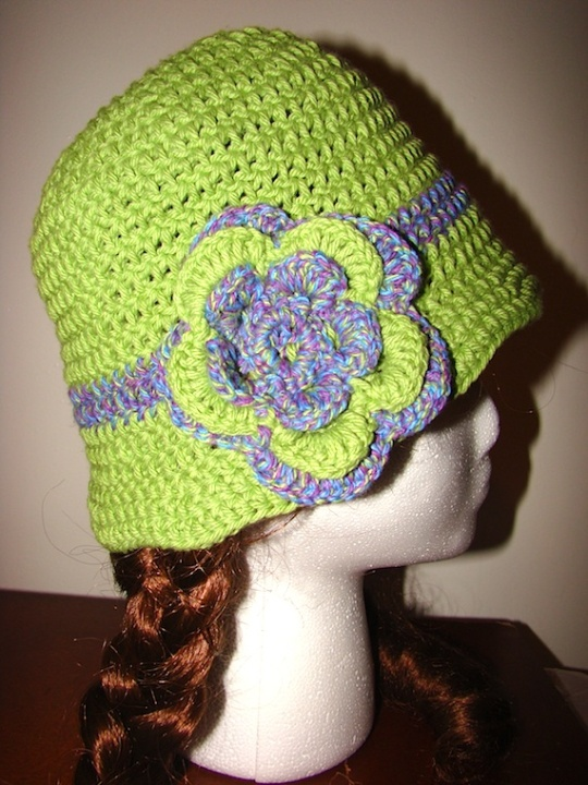 green hat with purple stripe and purple and green flower