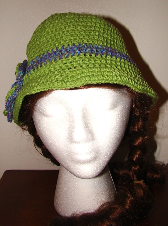 front view of green hat with purple stripe and flower