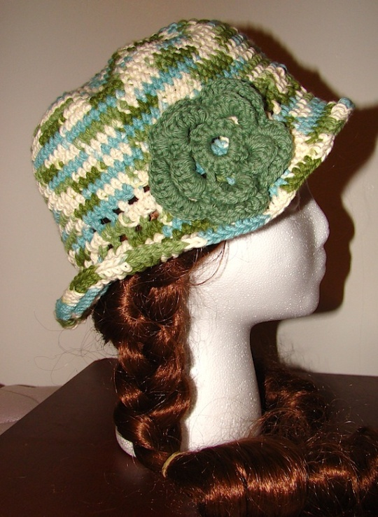 green and white multi colored sun hat with green flower