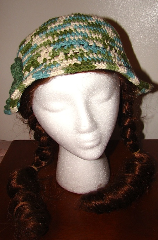 front view of green and white multi colored sun hat with green flower