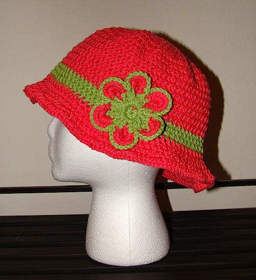 side view of pink floppy sun hat with green and pink flower