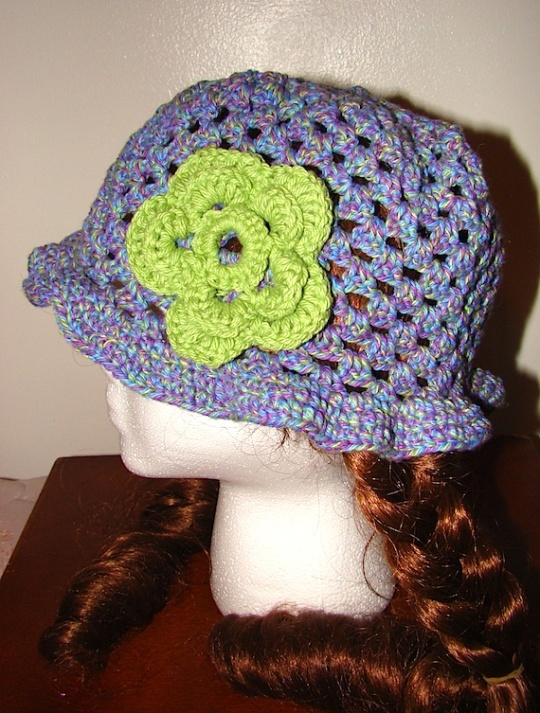 side view of purple open stitch sun hat with green flower
