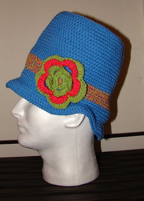 crochet blue top hat with rainbow stripe and green and pink flower