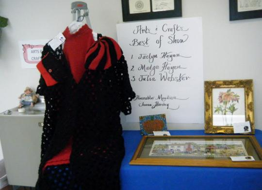Neldee crochet formal on display next to my mom's needle point with the list of Best In Show with Jaclyn Heyen as 1st