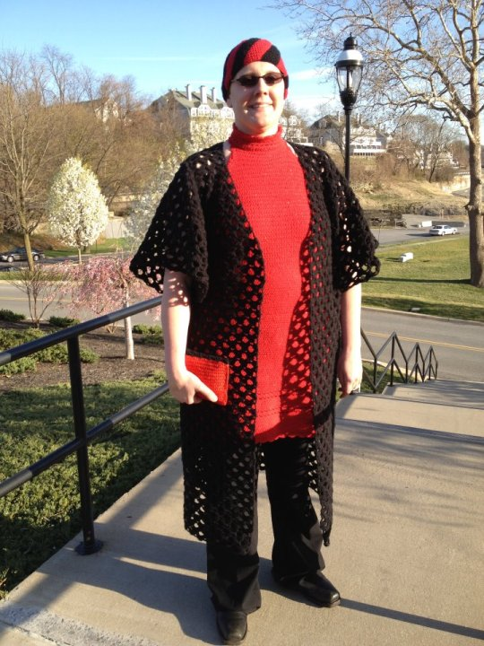 Crochet red dress top, black duster jacket, red and black clutch and swirly hat